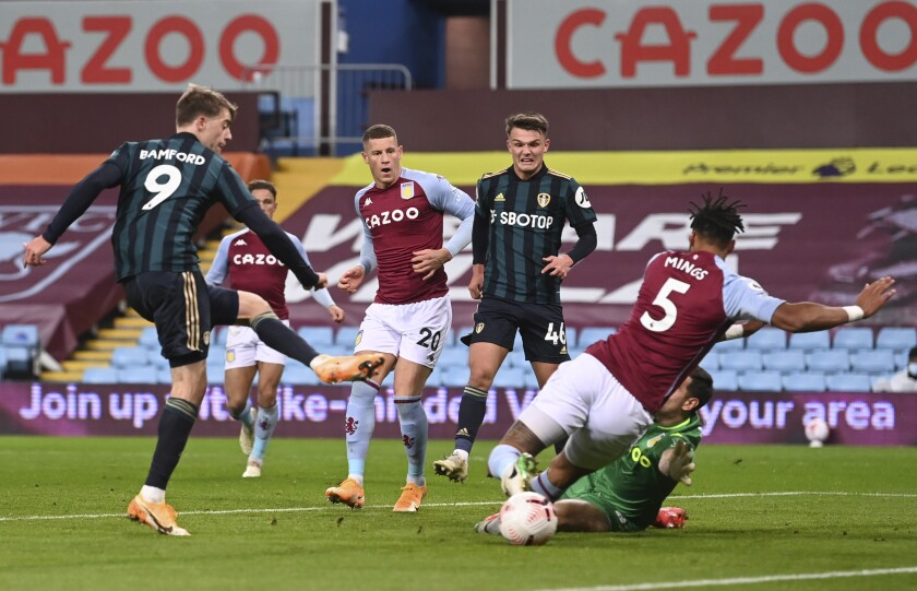Leeds United's Patrick Bamford, left, shoots to score during the English Premier League soccer match between Aston Villa and Leeds United at Villa Park in Birmingham, England, Friday, Oct. 23, 2020. (Laurence Griffiths/Pool via AP)