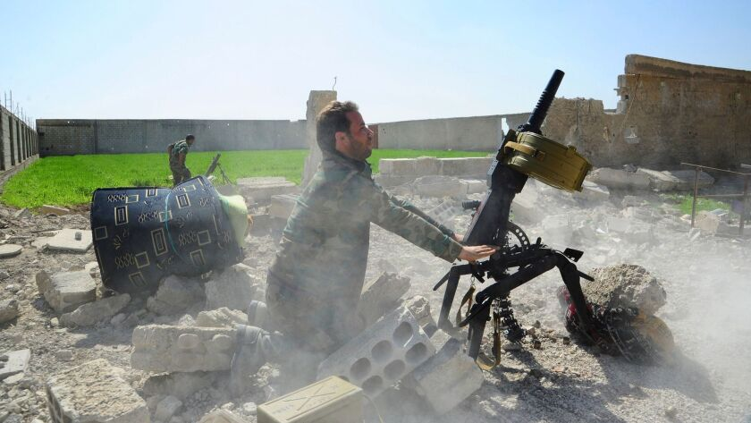 Photo released by Syrian official news agency SANA shows Syrian government soldiers firing a weapon during a battle against Syrian rebels in eastern Ghouta