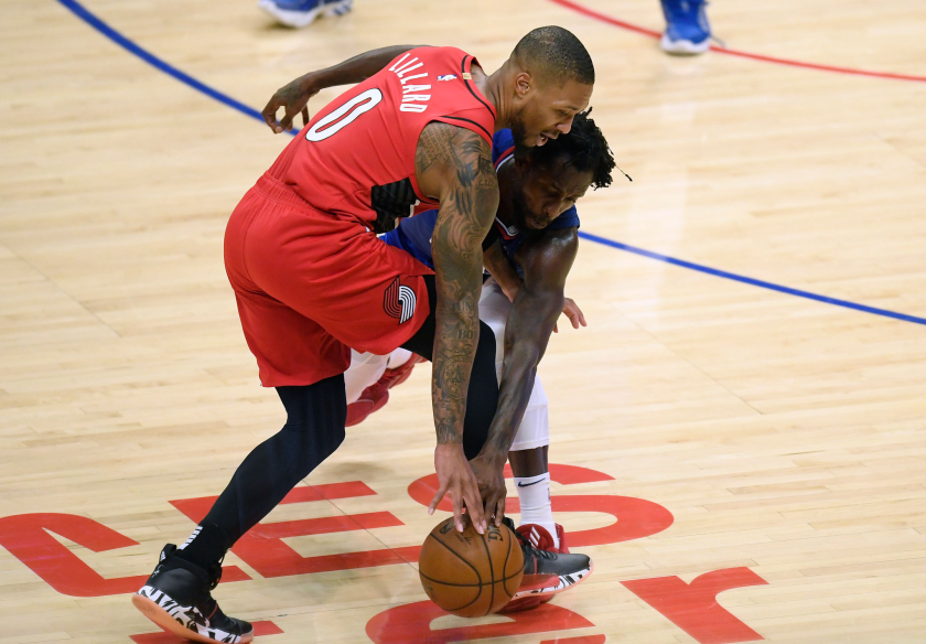 Clippers guard Patrick Beverley tries to steal the ball away from Portland Trail Blazers guard Damian Lillard.