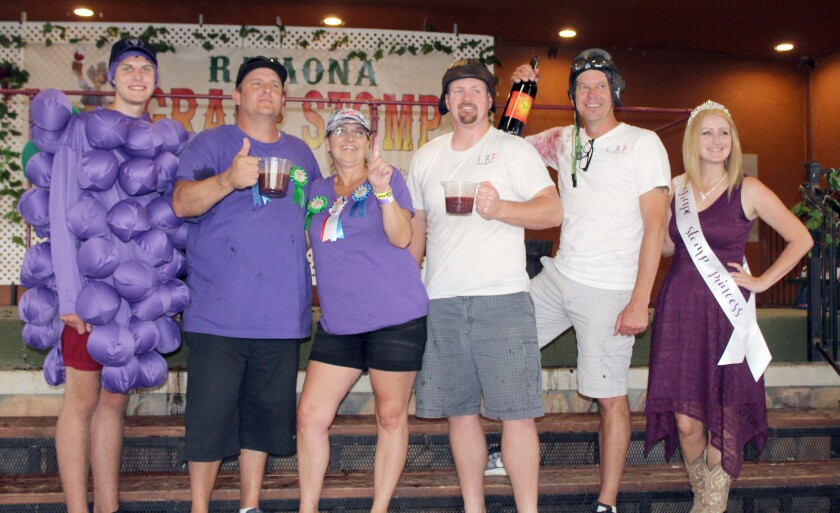 Toe Jammers stomper Lora Cicalo, Ramona Senior Center's executive director, shows her team is No. 1 as Toe Jamers swabber Lane Yuhl holds the team's cup of grape juice. Also pictured are second-place finishers Sean Hogan and Christian Davis, Grape Man Jacob Tretera and Grape Stomp Princess Allie Campbell.