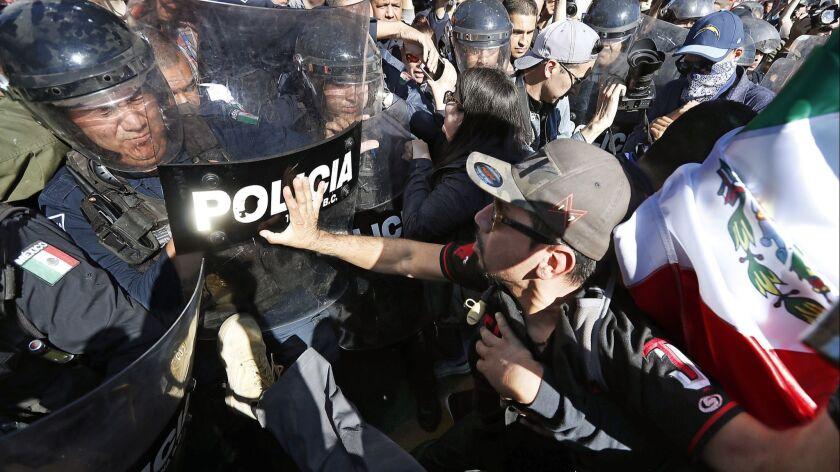 TIJUANA, MEXICO - NOV. 18, 2018. Protesters clash Sunday, Nov. 18, 2018, with police guarding a s