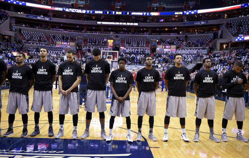 """Members of the Georgetown basketball team stand for the National Anthem wearing """"I Can't Breathe"""" t-shirts before an NCAA college basketball game against Kansas, Wednesday, Dec. 10, 2014, in Washington. (AP Photo/Nick Wass)"""