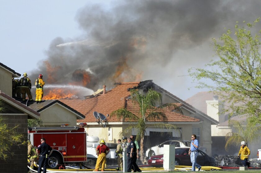 This photo shows the site of a military jet that crashed on a residential street in the desert community of Imperial, Calif., Wednesday, June 4, 2014. Witnesses say two houses caught fire after the crash. (AP Photo/The Imperial Valley Press, Chelcey Adami)