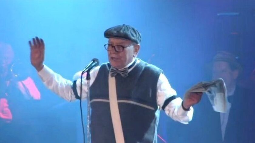 Billionaire investor Warren Buffett, dressed as a paper boy, sings at the Omaha Press Club Show.
