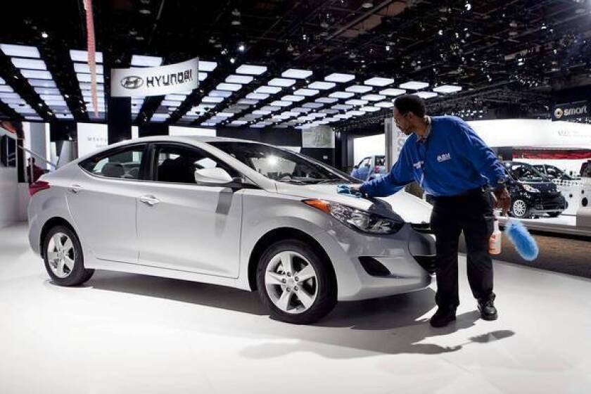 "Hyundai pitches its ""40 Mile Per Gallon Elantra"" without a government-mandated disclosure that the estimate is for highway driving only and that other measures are much lower, according to a lawsuit filed jointly by a car buyer and Santa Monica-based Consumer Watchdog. Above, a worker wipes down an Elantra at the 2011 Detroit auto show."
