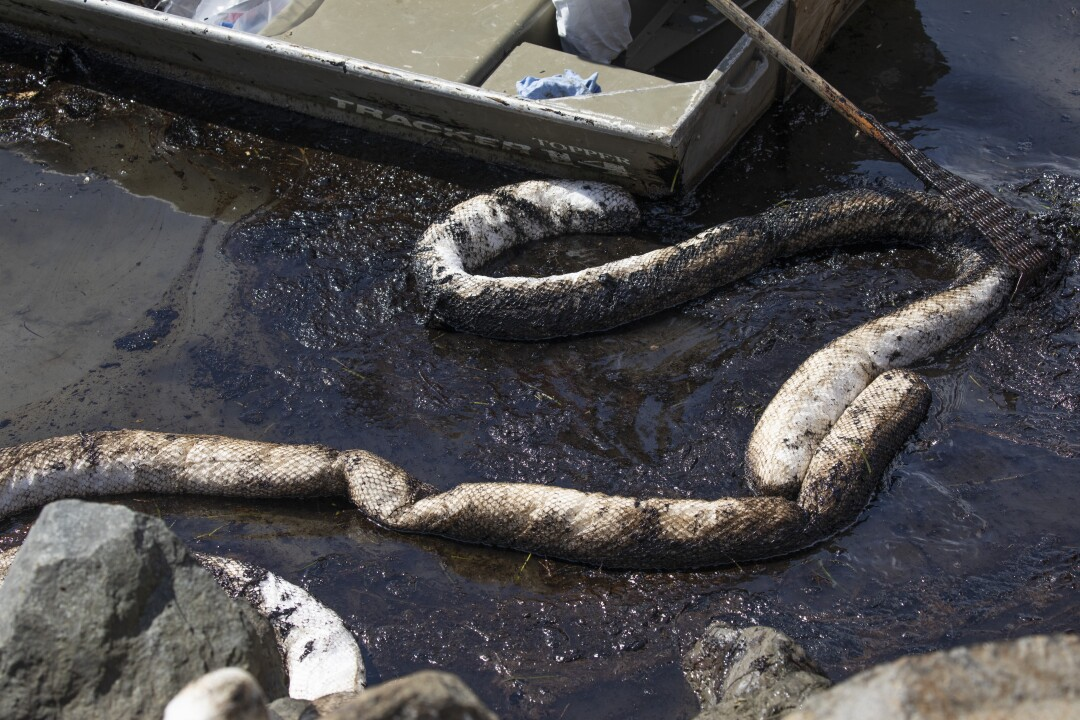 Oil absorbent booms are used by workers with Patriot Environmental Services to clean from the oil spill.