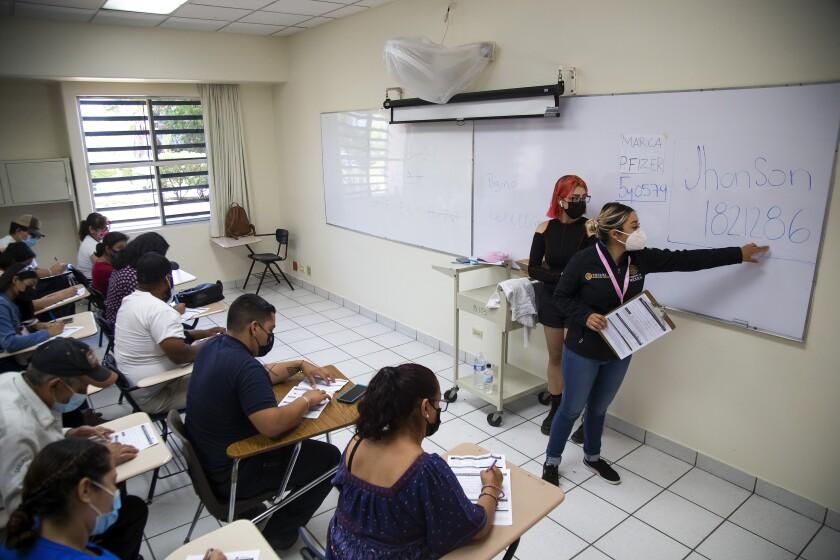 Ciudadanos que han recibido la vacuna son ayudados a llenar un documento