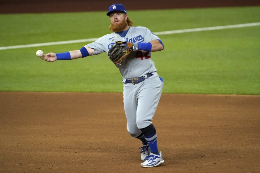 Los Angeles Dodgers third baseman Justin Turner throws to first to complete the ground out by Texas Rangers' Nick Solak in the sixth inning of a baseball game in Arlington, Texas, Friday, Aug. 28, 2020. (AP Photo/Tony Gutierrez)
