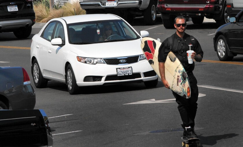 A surfboard-toting skateboarder threads through traffic in Hermosa Beach, where voters will decide whether to loosen a ban on oil and gas drilling.