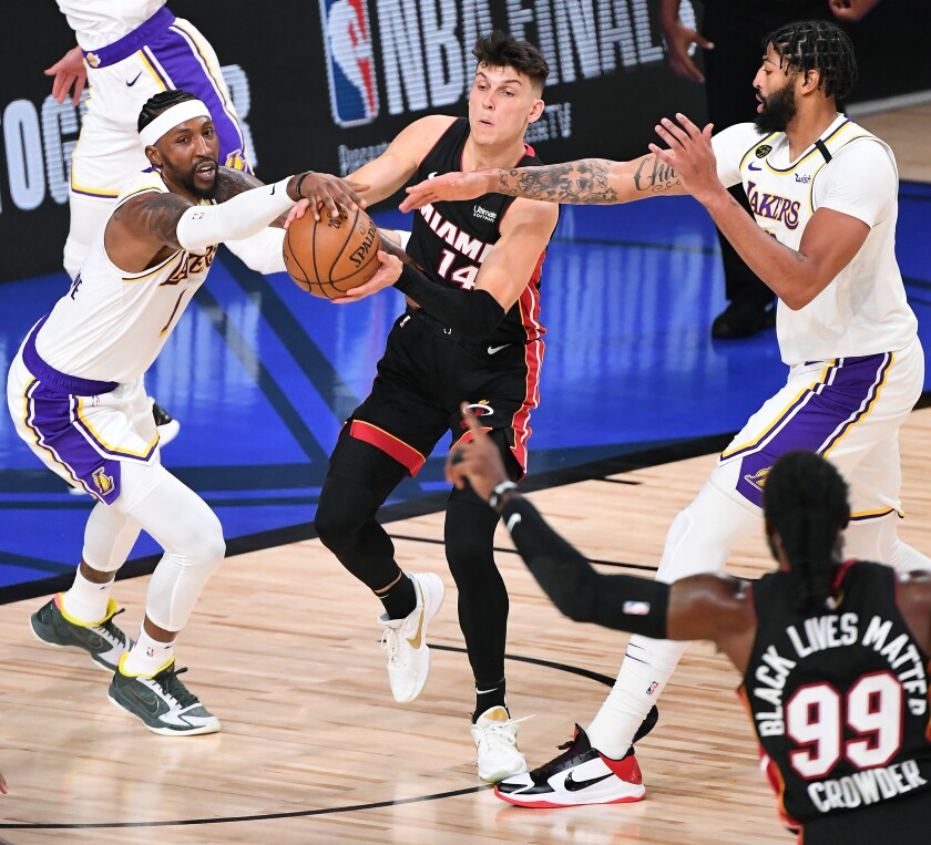 The Lakers' Kentavious Caldwell-Pope, left, and Anthony Davis apply defensive pressure to the Miami Heat's Tyler Herro.