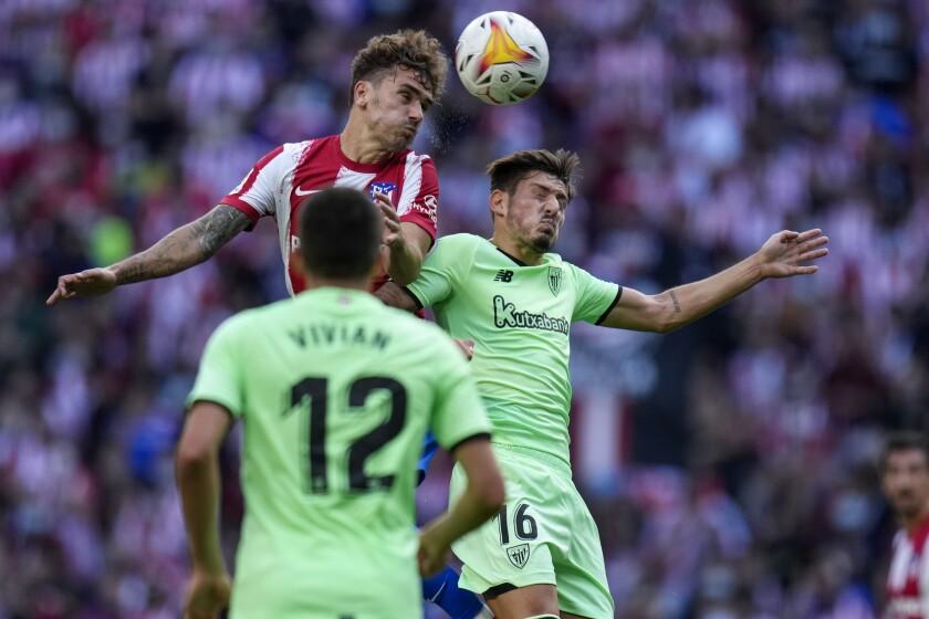 Atletico Madrid's Antoine Griezmann heads the ball past Athletic Bilbao's Unai Vencedor during a Spanish La Liga soccer match between Atletico Madrid and Athletic Bilbao at Wanda Metropolitano stadium in Madrid, Spain, Saturday, Sept. 18, 2021. (AP Photo/Manu Fernandez)