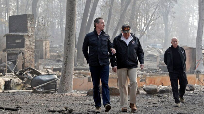 Then-Gov.-elect Gavin Newsom walks with President Trump and Gov. Jerry Brown last year in a neighborhood destroyed by the Camp fire in Paradise, Calif.