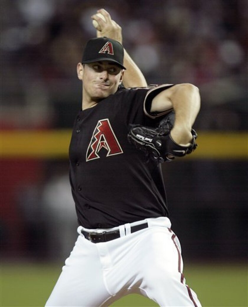 Arizona Diamondbacks' Daniel Hudson winds up to deliver a pitch against the Cincinnati Reds in the first inning of an MLB baseball game on Saturday, April 9, 2011, in Phoenix. (AP Photo/Paul Connors)