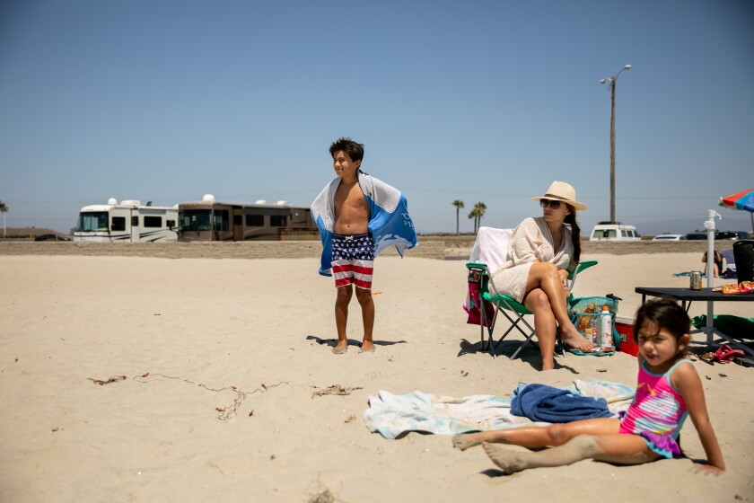 Cole Rivera, 12, of Chula Vista wears his American flag board shorts as he dries off next to his mother