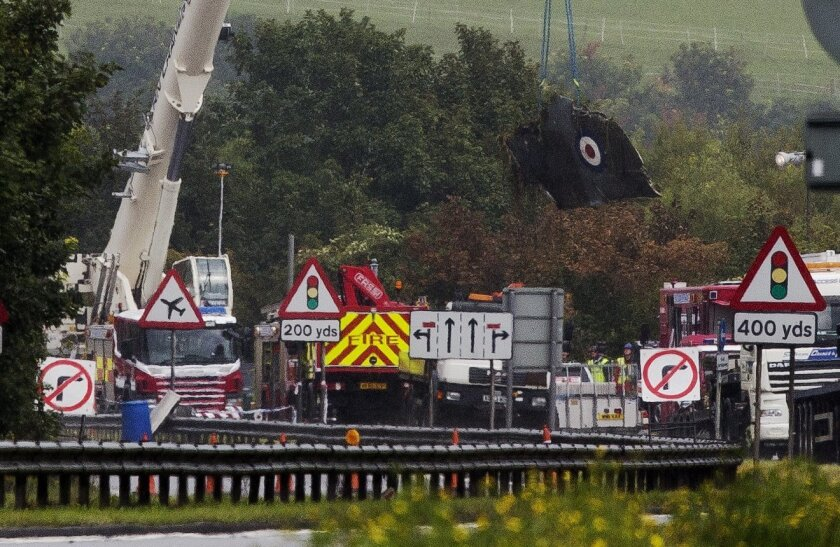 A crane lifts a section of the Hawker Hunter jet that crashed into a highway Saturday after it failed to pull out of a loop maneuver during the Shoreham Airshow, near Shoreham, England, about 75 kilometers (45 miles) south of London, Monday Aug. 24, 2015. Police said the death toll in the crash will probably rise as emergency workers probe wreckage on the freeway where the plane went down, plowing through cars on the road and exploding in a huge fireball. (AP Photo/Matt Dunham)