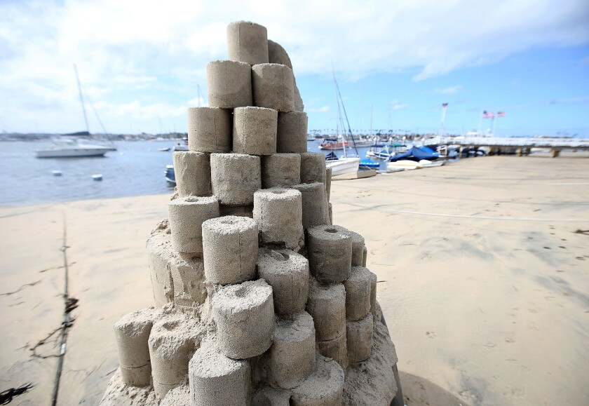 """A toilet paper tower titled """"Roll With It"""" by sandcastle artist Chris Crosson rises on Balboa Island in Newport Beach."""