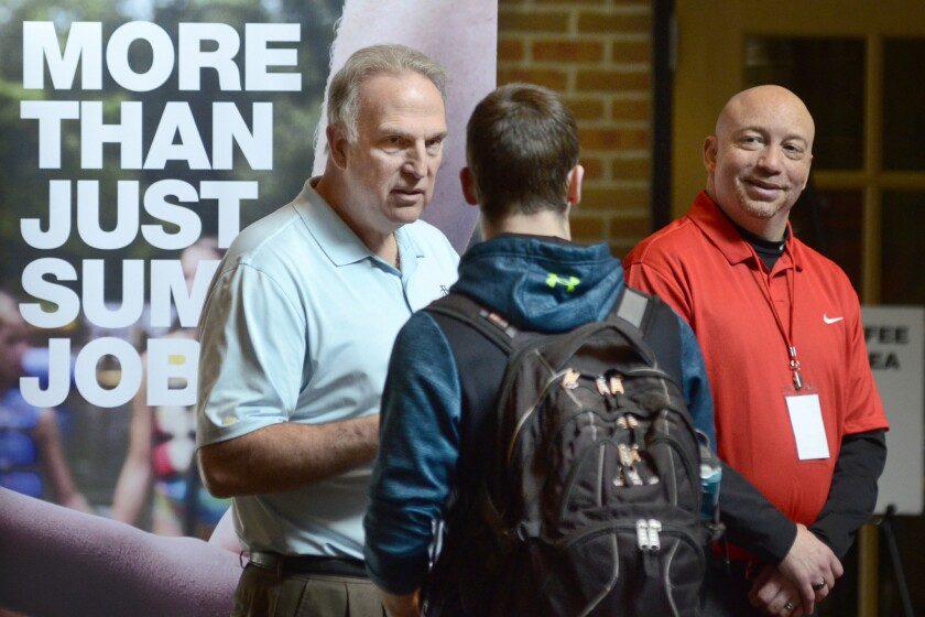 In this March 14, 2018, file photo, Dan Cieslak, left, a Human Resources representative for the Dunham's Distribution Center, and Warren Whitlow, a training manager, speak to students and other visitors during the Experience Indiana job fair event in the student center at Indiana Wesleyan University in Marion, Ind. The U.S. government issues the May jobs report on Friday, June 1.