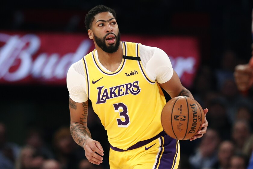 Lakers forward Anthony Davis brings the ball up court during a game.