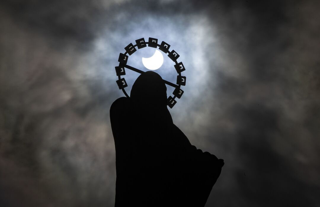 A statue of Our Lady, Star of the Sea on Bull Wall in Dublin, is silhouetted against the sky during partial eclipse.