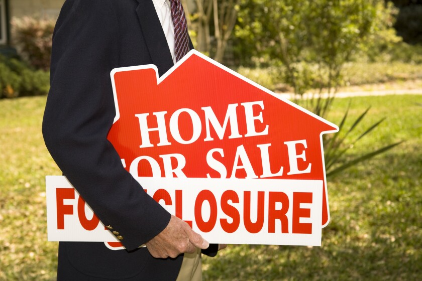 A foreclosure sign on top of a for-sale sign outside a home in Denver.
