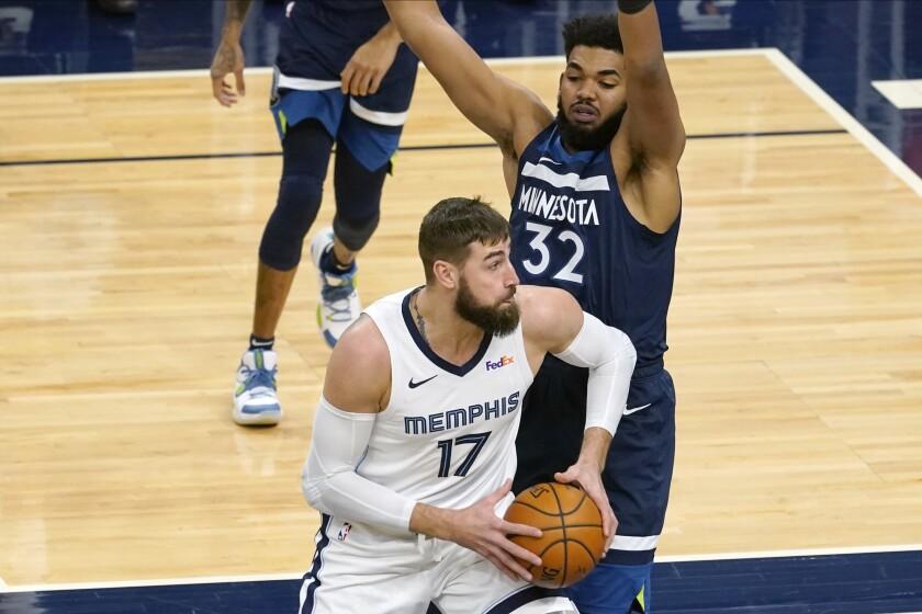 Memphis Grizzlies' Jonas Valanciunas (17) makes his way past Minnesota Timberwolves' Karl-Anthony Towns (32) in the first half of an NBA basketball game, Wednesday, Jan. 13, 2021, in Minneapolis. (AP Photo/Jim Mone)
