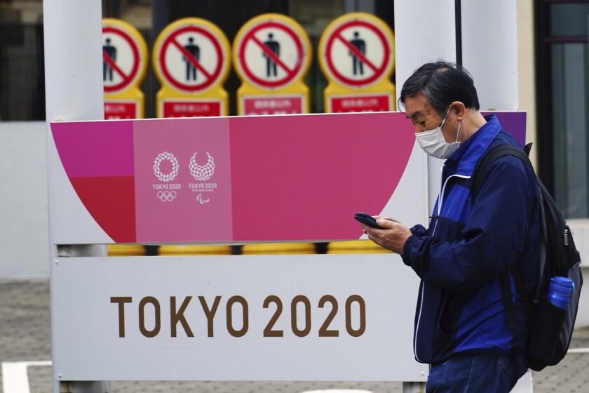 Un hombre con mascarilla para combatir los contagios de coronavirus pasa junto a un cartel de los Juegos Olímpicos