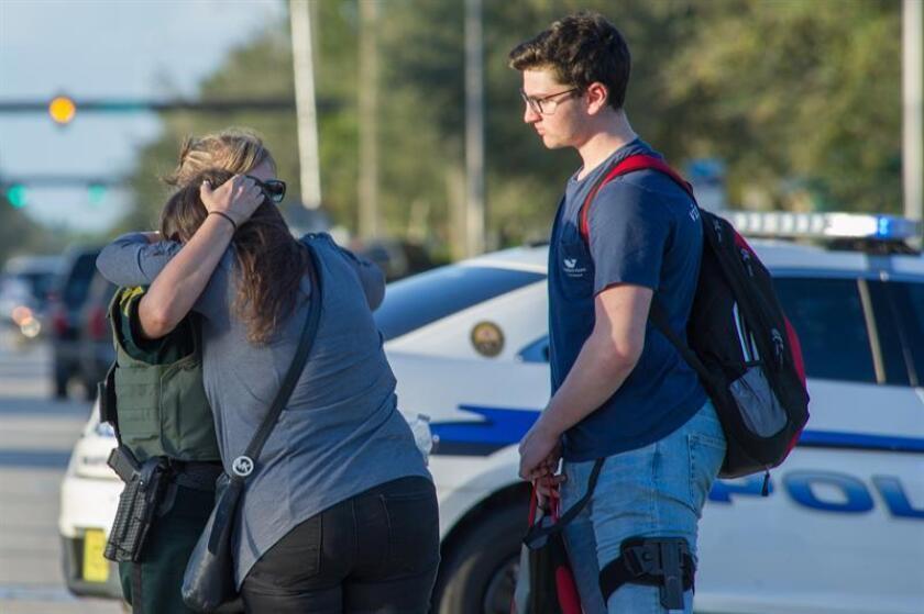 Una oficial de policía consuela a una mujer tras el tiroteo, donde un estudiante resultó herido de bala en un tobillo. EFE/Archivo