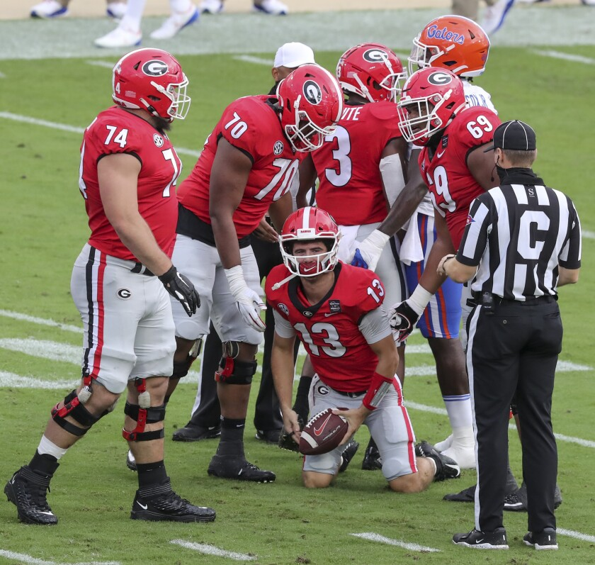 Georgia quarterback Stetson Bennett (13) gets up after he recovered his own fumble against Georgia during the first half of a NCAA college football, Saturday, Nov. 7, 2020, in Jacksonville, Fla. (Curtis Compton/Atlanta Journal-Constitution via AP)