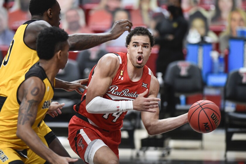 Texas Tech's Marcus Santos-Silva (14) attempts to pass the ball around multiple Grambling State players in the first half of an NCAA college basketball game in Lubbock, Texas, Sunday, Dec. 6, 2020. (AP Photo/Justin Rex)