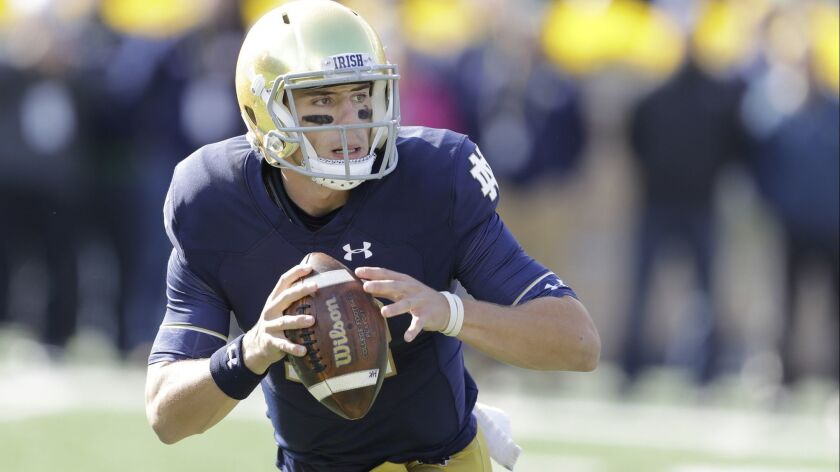 Notre Dame quarterback Ian Book (12) throws during the first half of an NCAA college football game a