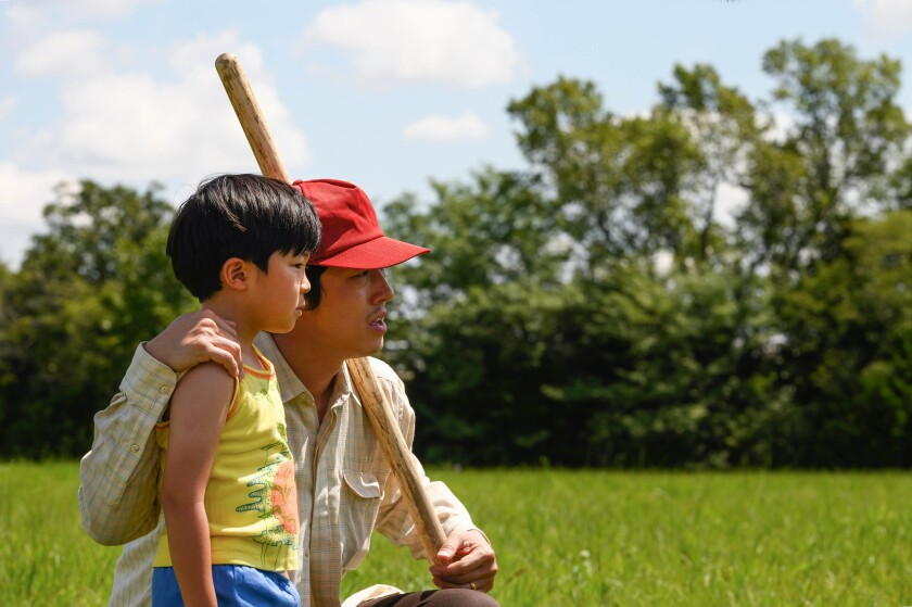 "Steven Yeun, holding a wooden stick, kneels in grass next to a boy in ""Minari."""