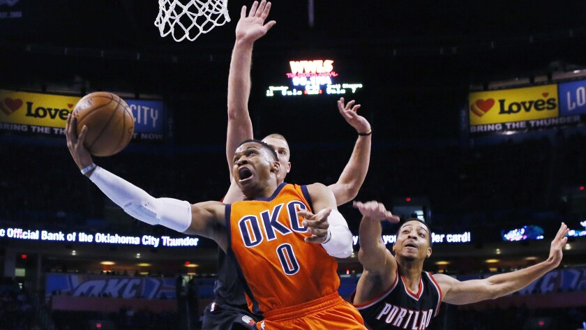 Thunder guard Russell Westbrook attempts a reverse layup against Trail Blazers center Mason Plumlee and guard C.J. McCollum, right, during the first quarter Sunday.