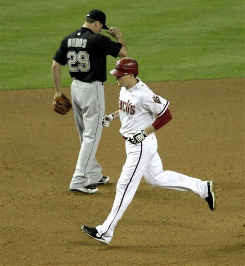 Arizona Diamondbacks' Kelly Johnson rounds third after hitting a solo home run as Florida Marlins' Greg Dobbs (29) looks away during the eighth inning of a baseball game against the Tuesday, May 31, 2011, in Phoenix. (AP Photo/Matt York)