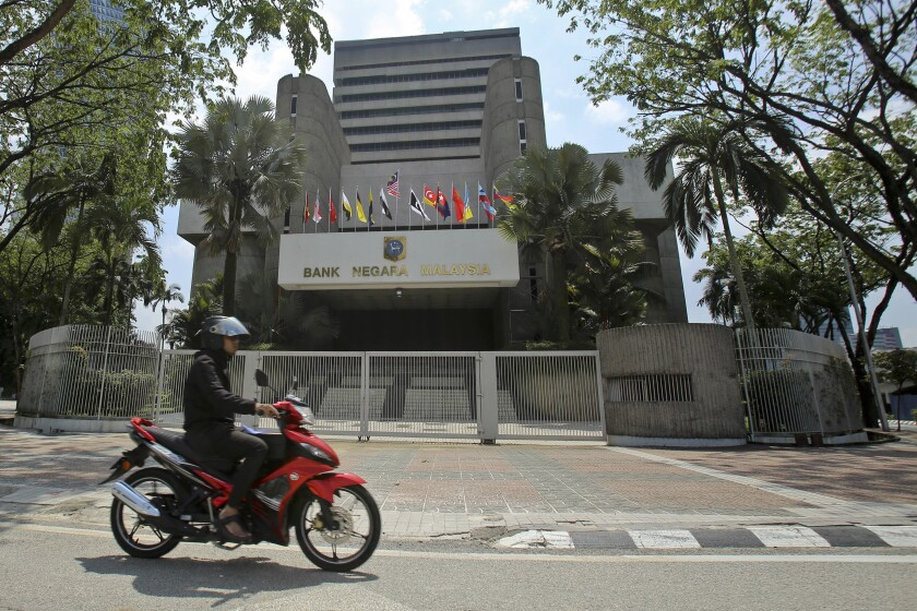 FILE - In this June 6, 2018, file photo, a motorcyclist rides past the Bank Negara Malaysia in Kuala Lumpur, Malaysia. Malaysia's central bank reduced its key overnight policy rate by 0.25 percentage points to 2.5% on Tuesday, March 3, 2020, citing worsening economic conditions from the virus outbreak in a growing number of countries. The central bank said it expects economic growth to be stunted in this quarter as tourism and consumer spending take a hit from weaker demand. (AP Photo/Sadiq Asyraf, File)