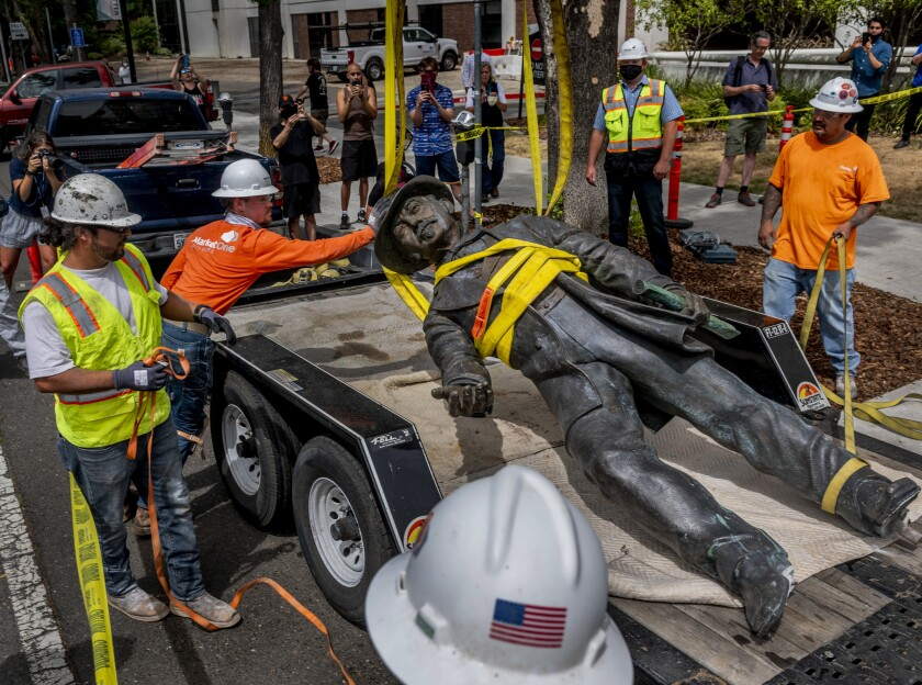 Workers remove a statue of John Sutter from a Sacramento hospital on Monday.