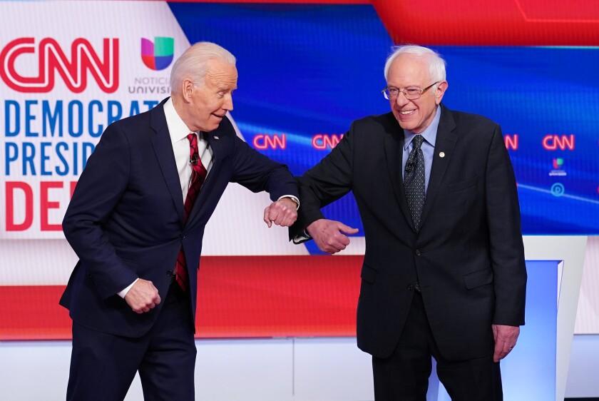 Joe Biden and Bernie Sanders greet each other with an elbow bump