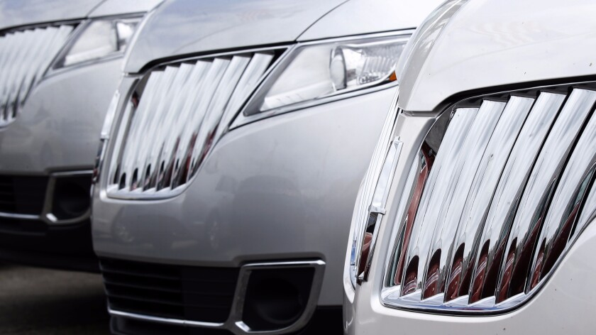 A row of 2014 Lincoln MKX SUVs are lined up on a dealer's lot.