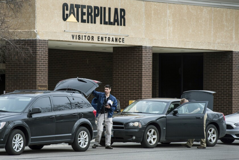 Federal officials gather at their vehicles as they continue to execute a search warrant at the Caterpillar, Inc. facility in Morton, Ill., one of three Caterpillar facilities they are searching in the Tri-County area Thursday, March 2, 2017.