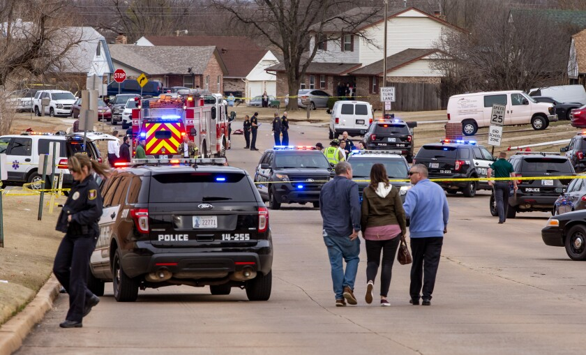 FILE - In this Monday, Feb. 3, 2020, file photo, emergency crews respond to a scene where a vehicle hit several Moore High School students in Moore, Okla. Moore High School is marking the one-year anniversary of the deaths of three members of its cross country team with gatherings of students inside the school, counselors for students and staff and therapy dogs. School Principal Mike Coyle said Wednesday, Feb. 3, 2021, that students and staff are also invited to write notes remembering the three, which will be placed in a time capsule later this spring. (Chris Landsberger/The Oklahoman via AP, File)