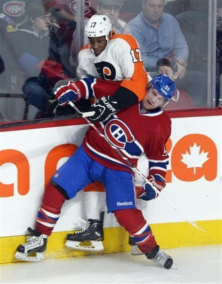 Montreal Canadiens' David Desharnais (51) collides with Philadelphia Flyers' Wayne Simmonds during the first period of an NHL hockey game in Montreal, on Saturday, Feb. 16, 2013. (AP Photo/The Canadian Press, Graham Hughes)