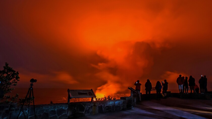 Red-hot lava spews skyward from the Kilauea volcano as visitors to Hawaii Volcanoes National Park observe from a safe distance.
