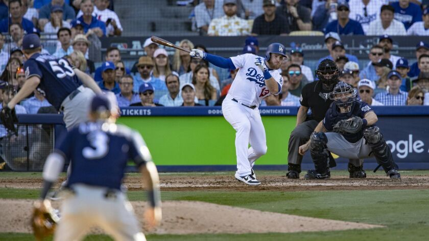 Dodgers first baseman Max Muncy hits an RBI single off Milwaukee Brewers relief pitcher Brandon Woodruff in the sixth inning.