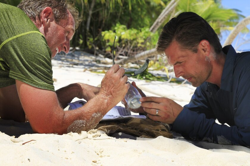 """This Aug. 2014 photo provided by the Discovery Channel, U.S. Sen. Jeff Flake, R-AZ, left and Martin Heinrich, D-N.M. work together and attempt to start a fire while surviving on a remote Eru island, part of the Marshall Islands for Discovery Channel's Rival Survival. Two U.S. senators from opposite sides of the political aisle spent a week marooned together on a remote island for a new reality show, """"Rival Survival."""" (AP Photo/Discovery Channel)"""