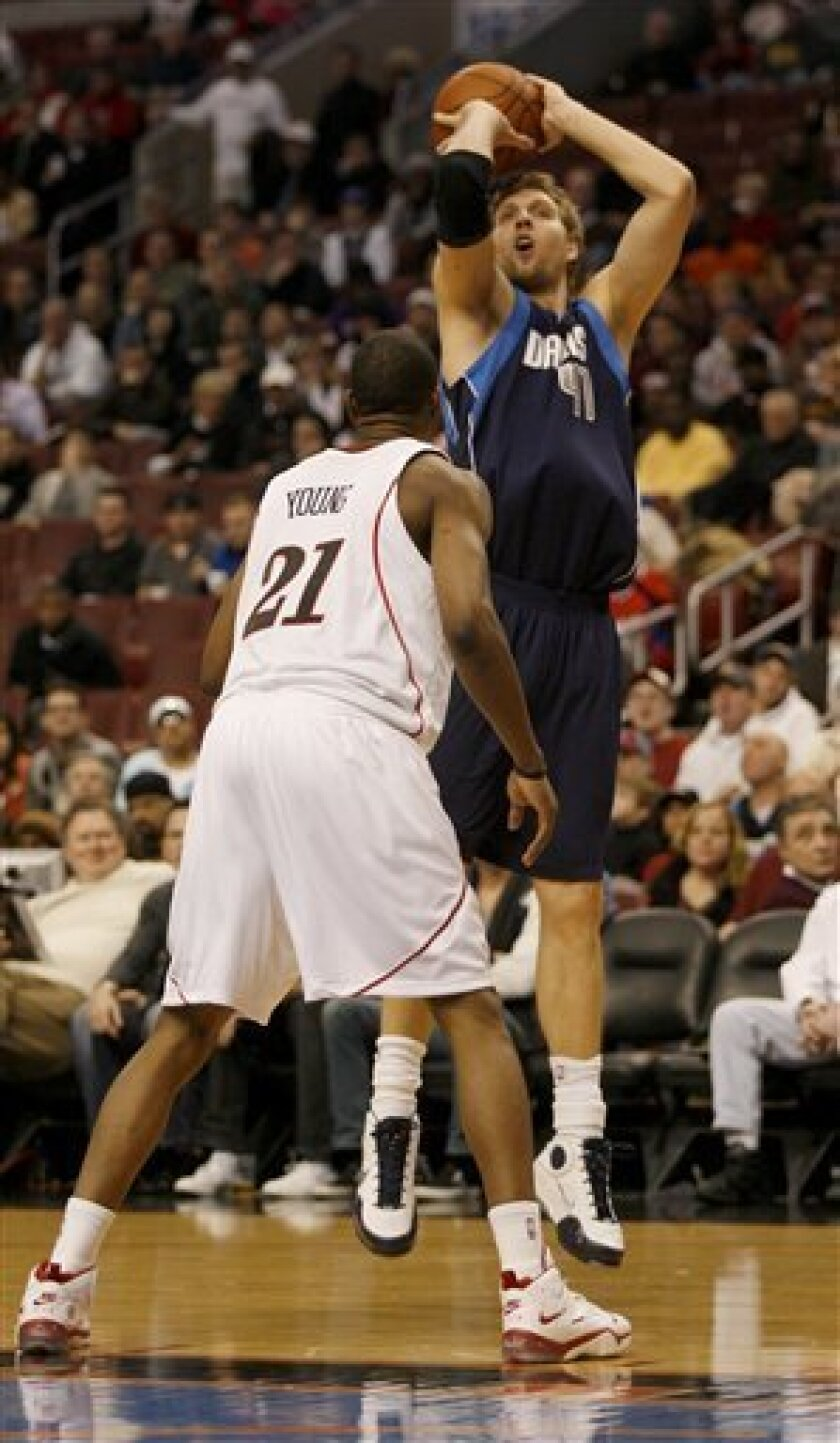 Dallas Mavericks' Dirk Nowitzki (41) shoots over and Philadelphia 76ers' Thaddeus Young (21) in the first period of an NBA basketball game Monday, Jan. 19, 2009, in Philadelphia. (AP Photo/H. Rumph Jr)