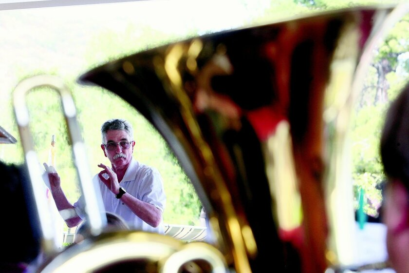 (left) Viewed through a tuba in the foreground, conductor Dean Hickman leads the Pomerado Community Band as they perform during the 15th Annual Southern California Community Band Festival and Arts and Crafts Market at Old Poway Park in Poway on Sunday. Photo Hayne Palmour IV