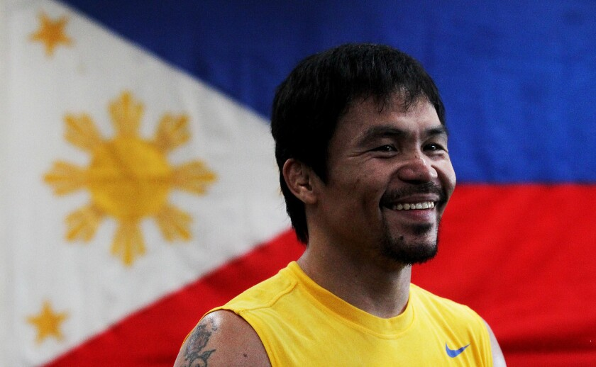 Boxer Manny Pacquiao smiles while being framed by the flag of the Philippines. He opened training camp at the Wild Card Boxing Gym in Los Angeles on Monday.