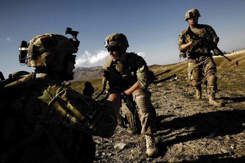 Sgt. Christopher Lee of Beverly Hills, left, and Pvt. Tyler Hartzheim of Palos Verdes, center, and other U.S. soldiers take part in an operation in support of Afghan troops in Wardak province.