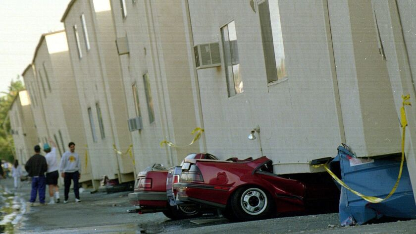 Cars are squashed underneath collapsed apartment buildings in the 19100 block of Victory Boulevard in Tarzana after the 1994 Northridge earthquake. The buildings were declared unihabitable.