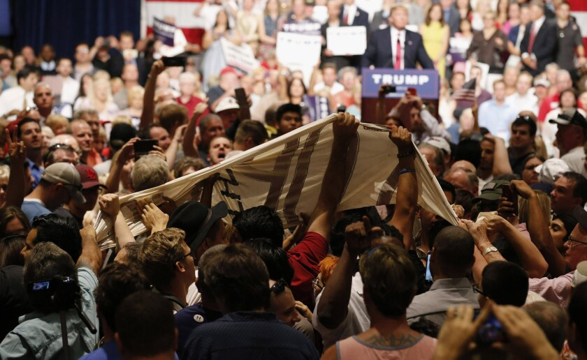 Supporters of Republican presidential candidate Donald Trump pull down a banner from immigration rights protesters as Trump speaks in Phoenix last summer.