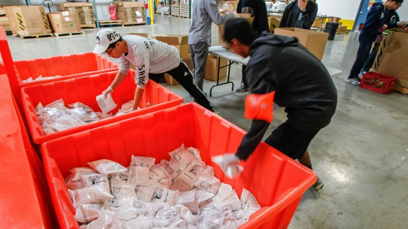 The Jacobs & Cushman San Diego Food Bank said it helps more than 28,000 low-income armed forces personnel and veterans. Here, volunteers package oatmeal at the food bank's main warehouse on Nov. 22, 2016.